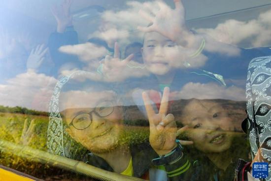 9月2日,校车上的学生们开心地向窗外打招呼。新华社发(王紫轩 摄)