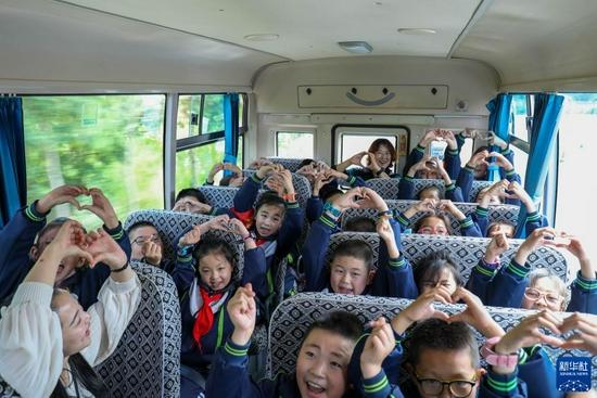 """9月2日,渭州学校的学生和老师在校车上一起""""比心""""。新华社发(王紫轩 摄)"""