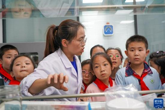 9月2日,在甘肃省定西市陇西县的陇西药圃园,技术人员带领渭州学校的学生参观实验室。新华社记者 郎兵兵 摄