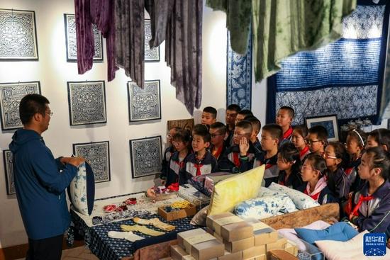 9月2日,胡家大院扎染体验馆的工作人员为渭州学校的学生们讲解扎染知识。新华社发(王紫轩 摄)