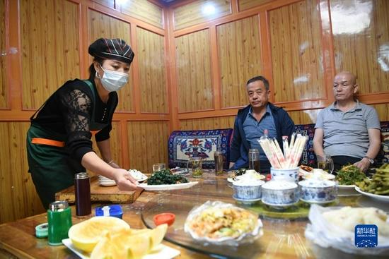 甘肃甘南卓尼县木耳镇力赛村村民李日占草(左)在自家的农家乐里为客人上菜(9月11日摄)。新华社记者 陈斌 摄