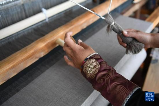 加科村村民周毛吉使用传统木式纺织机编织手工艺品(9月9日摄)。新华社记者 陈斌 摄