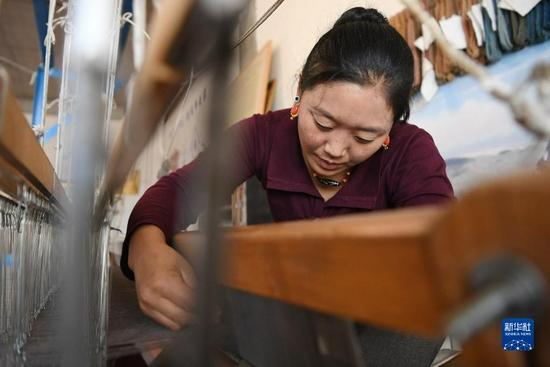 加科村村民拉姆吉检查纺织机(9月9日摄)。新华社记者 陈斌 摄