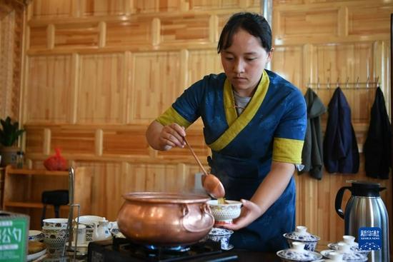 甘肃甘南卓尼县木耳镇力赛村村民拉姆卓玛在自家的农家乐里为客人盛汤(9月11日摄)。新华社记者 陈斌 摄
