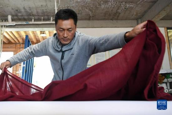 加科村村民拉毛杰在藏族手工艺品车间里整理布料(9月9日摄)。新华社记者 陈斌 摄