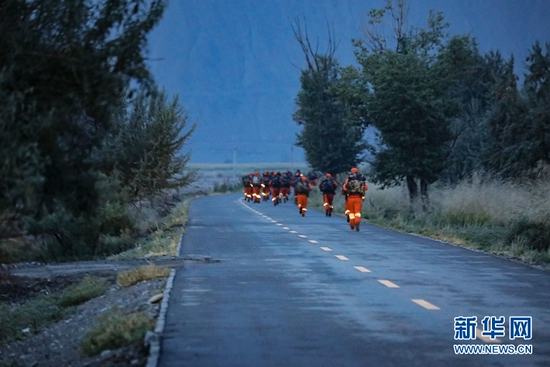 参赛队员在公路上负重奔跑。新华网发 (胡宇 摄)