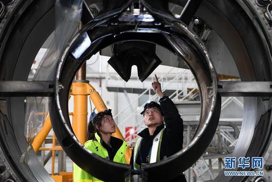 1月4日,在东航技术甘肃分公司机库,师父杨杰男给杨佳郁(左)讲解飞机发动机舱构造。