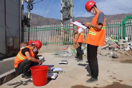 裁判正在对路基灌砂法检测进行计时 摄影:程诚