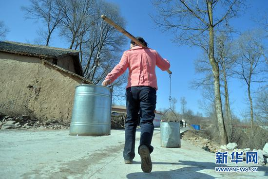 甘肃省渭源县田家河乡元古堆村的村民在引洮工程一期的自来水还未到达家中之前从村里唯一的水源往家里担水。(新华社记者范培珅2014年12月28日摄)