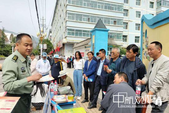 图为宕昌县人武部政委胡义文为家长答疑解惑。