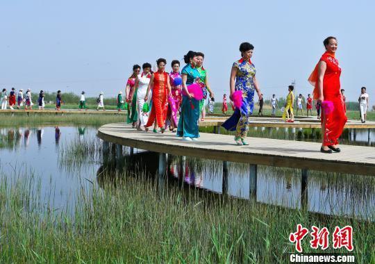 图为来自甘肃多地的200多名母亲身穿各式旗袍表演旗袍秀。 王将 摄