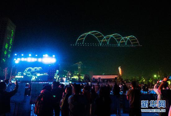 5月5日晚,兰州市民观看无人机编队展示的兰州地标中山桥图案。新华社发
