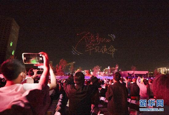 5月5日晚,兰州市民用手机拍摄无人机编队展示的图案。新华社发