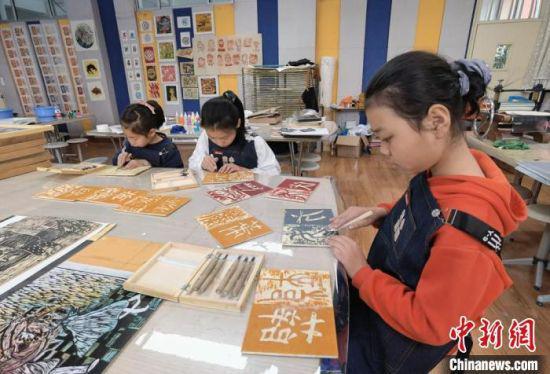 4月下旬,兰州市城关区安乐村小学学生制作木刻版画。(资料图) 刘玉桃 摄