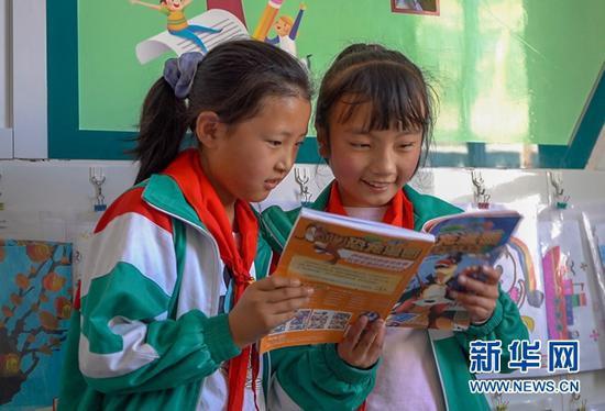 5月12日,芮芮(右)和同学在班级图书角读课外读物。新华社记者 郎兵兵 摄