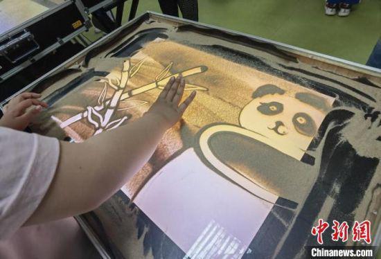 图为学生用沙子创作竹子和大熊猫。 高展 摄