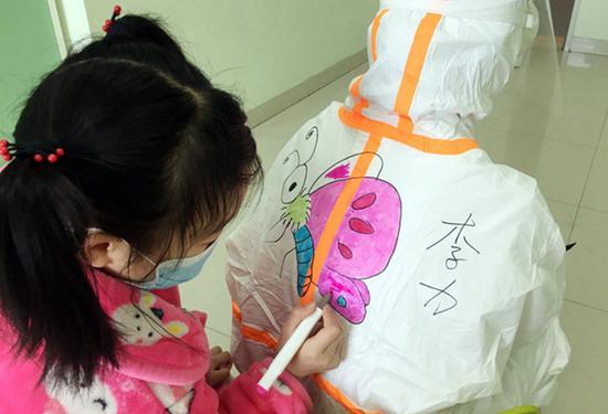 一名小朋友在医护人员的防护服上涂色。