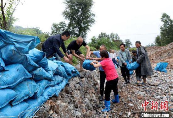 2020年8月17日,陇南灾害后,救援人员在现场加强堤坝安全。(资料图) 陇南市委宣传部供图 摄