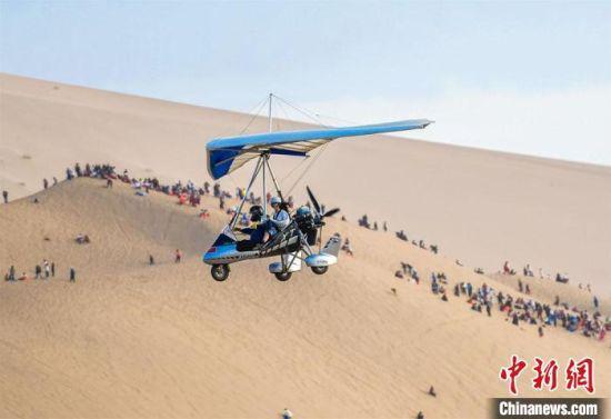 图为游客乘坐滑翔机从空中鸟瞰大漠美景。 王斌银 摄