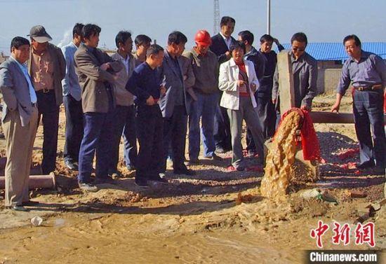 2008年9月,王惠玲和职工见证了山丹县新打的供水机井通水,该供水井解决了长城新村居民用水难问题。 雷华 摄