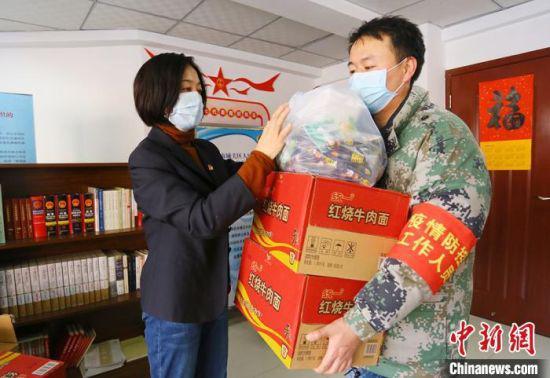 图为兰州市城关区草场街街道党工委副书记王芝萍给卡口点人员分发物资。 高展 摄