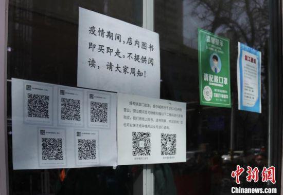 """图为兰州一书店,在门口张贴温馨提示及线上""""服务群""""信息。 闫姣 摄"""