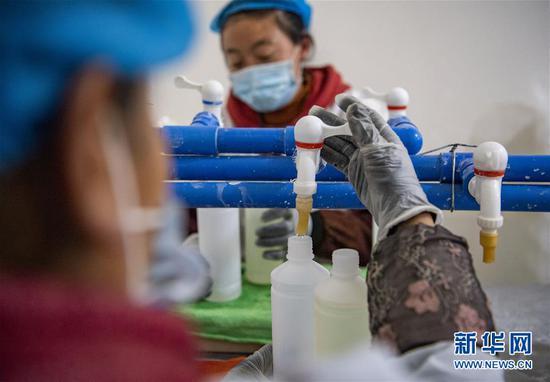 在西藏拉萨一家企业,复工后的生产车间里,工人在灌装消毒液(2月17日摄)。 新华社记者 孙非 摄