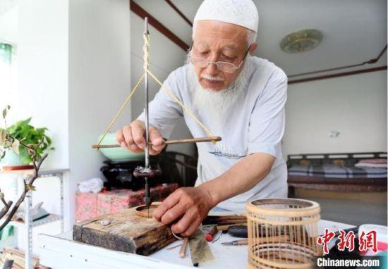 """7月中旬,甘肃天水市""""竹雕大师""""吴云生借助工具手工打眼。 高展 摄"""