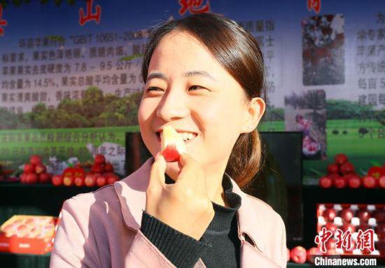 10月17日,第四届中国苹果产业大会在甘肃庆阳举行。图为民众品尝庆阳苹果。 高展 摄