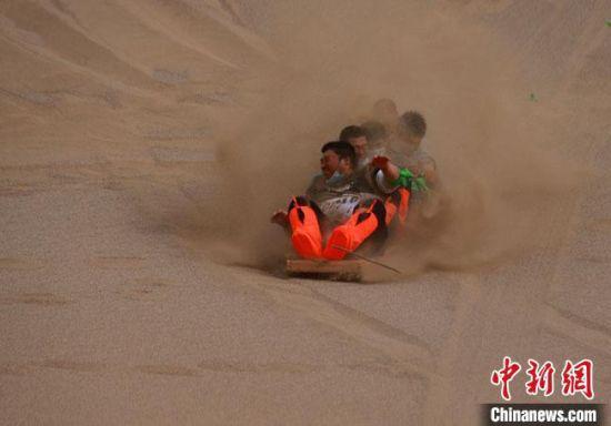 6月13日,敦煌鸣沙山月牙泉景区举办滑沙比赛。 冯豆 摄