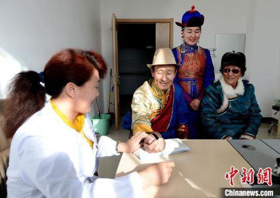 图为甘肃酒泉市肃北县蒙古族女医生斯琴(左)接诊患者。(资料图)肃北县委宣传部供图