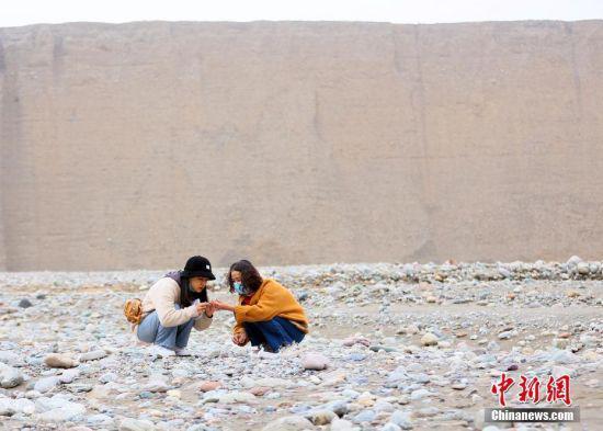 4月24日,甘肃酒泉洪水河大峡谷内,游客在捡奇石。