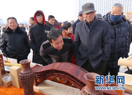 当地群众在观看榫卯木制手工作品(刘欣瑜 摄)