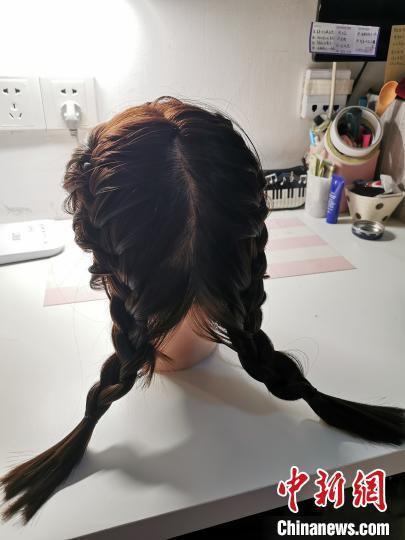 图为年轻妈妈在发型模型上开展练习。 崔琳 摄