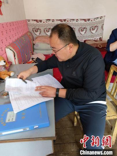 """2019年7月17日,邱军在填写""""两不愁、三保障""""核查表。(资料图) 华池县委宣传部供图"""