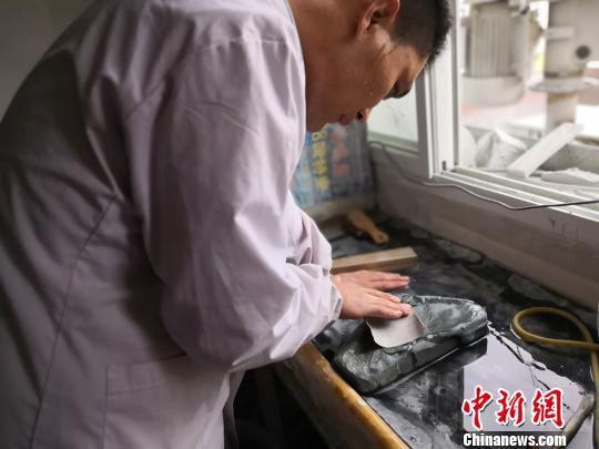 3月21日,兰州市大沙坪上川村,甘肃洮砚艺人黄炳强在自己的工作室对一块洮砚石进行打磨抛光。 杨娜 摄