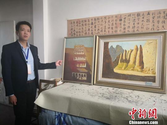 图为牛浩东介绍他的绘画代表作品《敦煌印象》与《黄河石林》。 崔琳 摄
