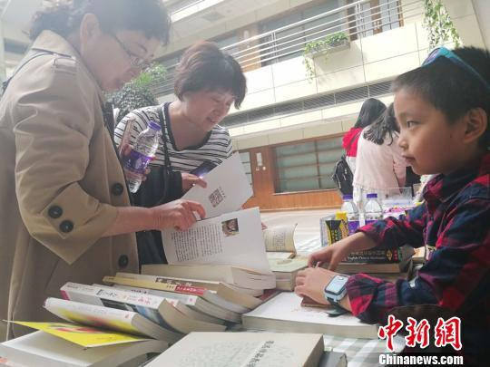 """在主会场之外,读者读书会还设置了闲置图书置换专区,6岁的小学生王之藩为他和爸爸的闲置图书找到了一位""""新主人""""。 史静静 摄"""