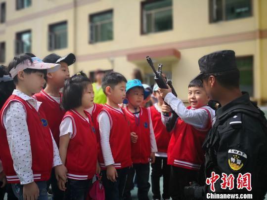 图为特警队员指导孩子们近距离感受真枪。 魏建军 摄