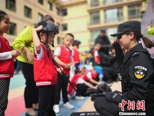 图为学生戴上头盔拿着警棍给特警队员敬礼。 魏建军 摄