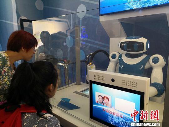 """图为家长和孩子体验绘画机器人,将两人合影画出来,定格""""幸福瞬间""""。 魏建军 摄"""
