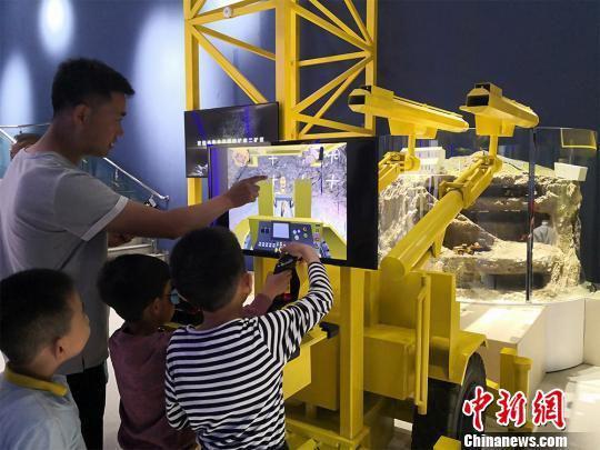 """图为家长陪同孩子操作智能""""采矿机器人"""",体验采矿乐趣。 魏建军 摄"""