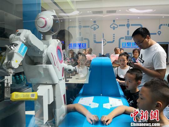"""6月1日,甘肃科技馆举办""""玩转科学欢度六一""""系列活动。各种智能机器人""""组团""""伴儿童们过节。图为智能售货机器人扮起""""服务员""""给孩子们卖零食。 魏建军 摄"""