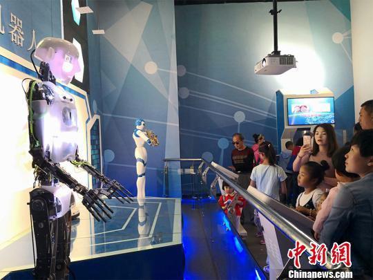 """图为两个机器人""""舞者""""精彩尬舞,吸引众人围观。 魏建军 摄"""