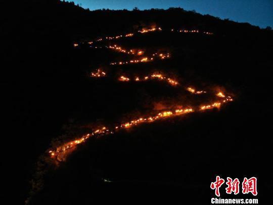 """6月14日至18日,第三届陇南文县白马人·民俗文化旅游节举行。图为火把星星点点从山顶奔腾而下,顺着蜿蜒山路呈现""""S""""形。 杨艳敏 摄"""