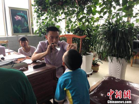6月下旬,在甘肃天水市秦安县的一家诊所里,乡村医生马启红每天五点半拄着拐杖准时接诊,来自甘肃、宁夏、新疆等地的患者此时已在门口排起了长龙。 徐雪 摄