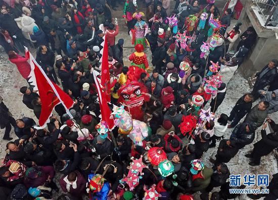 2月17日,在甘肃省陇南市武都区鱼龙镇卯家庄村,当地村民观看高山戏演员在村内巡游表演(无人机拍摄)。