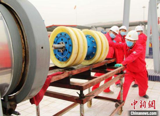 图为基层输油站员工将清管器从管道收球筒取出、并清理杂质。 石建强 摄