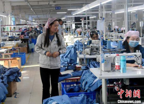 甘肃榕发服装智造公司的工作车间 ,该车间缝一组组长张桃玉正在工作中。