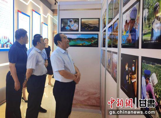 6月22日,甘肃省市场监管系统庆祝中国共产党成立100周年书画摄影艺术品展启动。图为观展者在作品前仔细品味。史静静 摄